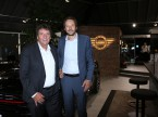 Kurt Egloff, CEO BMW Schweiz (links), und Olivier Muller, Direktor Mini, im neu gestalteten Mini-Pavillon der Auto-Graf AG in Meilen ZH; im Hintergrund das neue, zweidimensionale Mini-Logo.